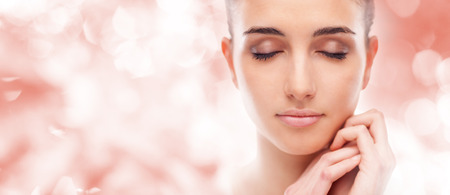 radiant: Beautiful young woman touching her radiant face skin with eyes closed Stock Photo