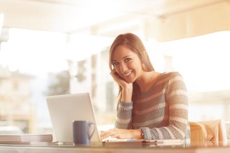 jovenes estudiantes: Mujer joven sonriente que trabaja en el escritorio de oficina con su computadora portátil Foto de archivo