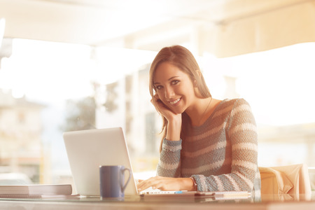 woman relaxing: Smiling young woman working at office desk with her laptop