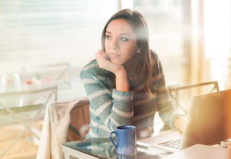 mujer pensando: Mujer pensativa con la mano en la barbilla trabajando con su portátil Foto de archivo