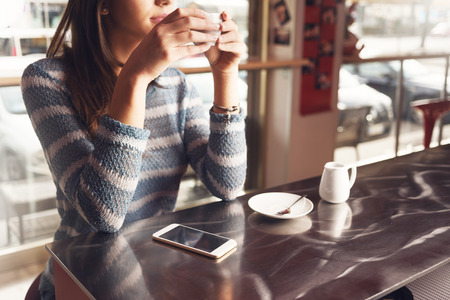 hot beverage: Pensive young woman at the bar having a cup of coffee