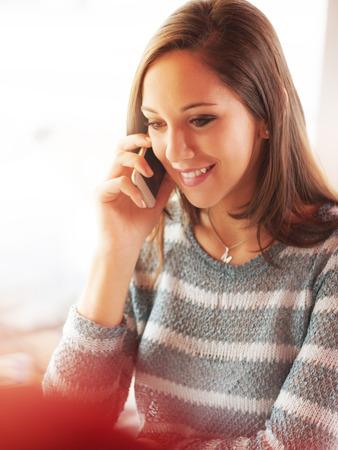 persona llamando: Beautiful young girl having a phone call sitting next to a window Foto de archivo