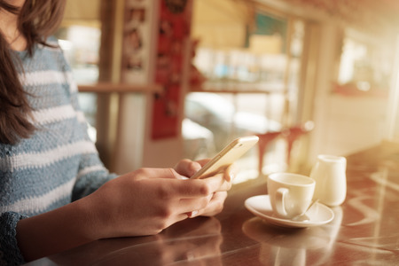 Woman leaning on the bar counter and text messaging with her mobile hands close up photo