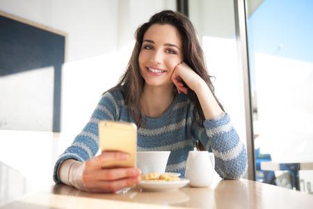 Enthousiaste femme réseautage social avec son téléphone intelligent au café