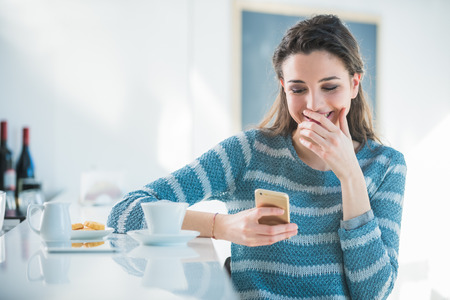 Cheerful woman at the bar reading funny messages on her mobile phone photo