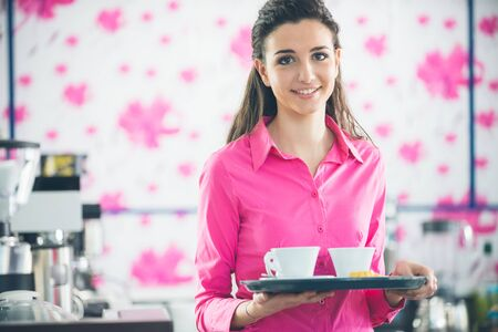 waitress: Young smiling waitress in pink shirt serving coffee at the bar floral wallpaper on background Stock Photo