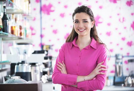 camisa: Barista sonriente hermosa que presenta en una m�quina de caf� caf� en el fondo Foto de archivo