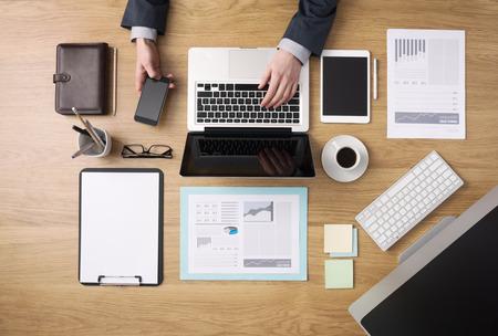 Homme d'affaires travaillant sur son ordinateur portable et en utilisant un téléphone mobile avec de la paperasse et des rapports financiers autour dessus de bureau vue
