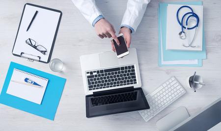 医師のオフィスの机で働いて、モバイル タッチ スクリーン携帯電話コンピューターおよび平面図中の医療機器を使用して
