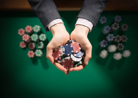 Elegant male casino player holding a handful of chips with green table on background hands close up top view photo