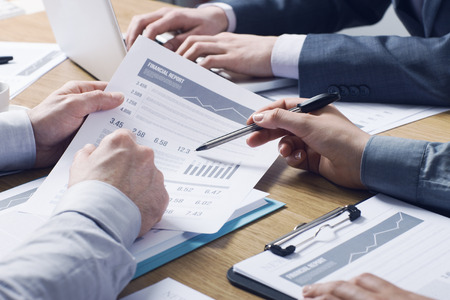 Business professionals working together at office desk hands close up pointing out financial data on a report