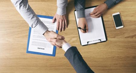 entrevista de trabajo: La contrataci�n de los empleadores y de dar un apret�n de manos al candidato despu�s de las manos para entrevistas de trabajo de cerca la vista superior Foto de archivo