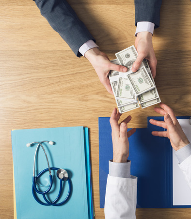 bribing: Male patient having a medical visit and bribing a greedy doctor with a lot of money top view unrecognizable people Stock Photo