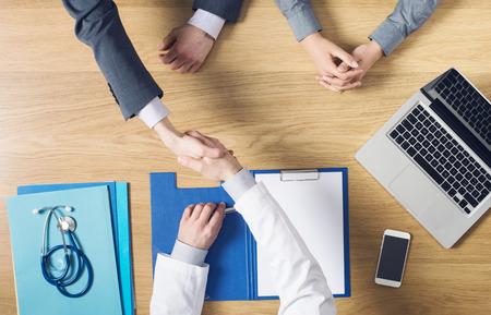 Arts die een handdruk aan zijn patiënt tijdens de vergadering op zijn bureau tijdens een bezoek vertrouwen en tevredenheid-concept Stockfoto