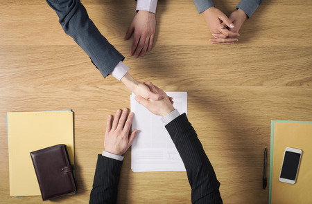Business people at office desk handshaking after signing an agreement hands top view unrecognizable people Foto de archivo