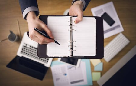 zeitplan: Geschäftsmann, der am Büroschreibtisch und der Anmerkungen notiert auf seiner Agenda Laptop und Finanzbericht auf den Hintergrund Ansicht von oben. Lizenzfreie Bilder