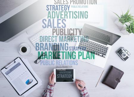 Homme d'affaires travaillant au bureau et en utilisant un des concepts de marketing numérique de la tablette et texte d'affaires qui sortent de l'écran de la tablette