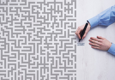 Businessman entering a maze and holding a marker business strategy and challenge concept Stock Photo