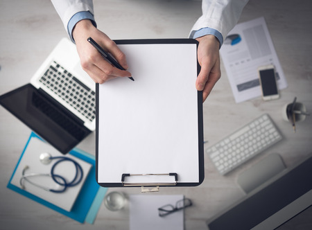 Doctor writing medical records on a blank sheet and holding a clipboard medical equipment and desktop on background top view Stock Photo