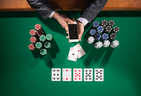 casino dealer: Elegant male poker player using a smartphone cards and chips stacks all around green table top view