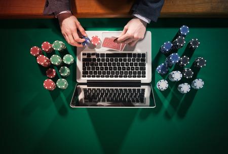 Man jouer au poker en ligne avec un ordinateur portable sur une table verte avec des puces tout autour vue de dessus qu'il regarde ses cartes