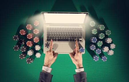 Les mains de joueurs en ligne avec un ordinateur portable et de la pile de jetons tout autour sur le vert vue de dessus de table, il pointe vers l'écran d'ordinateur Banque d'images