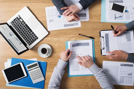 szakvélemény: Üzletemberek csapat dolgozik együtt irodai íróasztal laptop tablet pénzügyi papírmunka és jelentések felülnézet