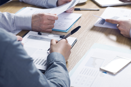 business efficiency: Business people team working together at office desk with financial data and paperwork teamwork concept
