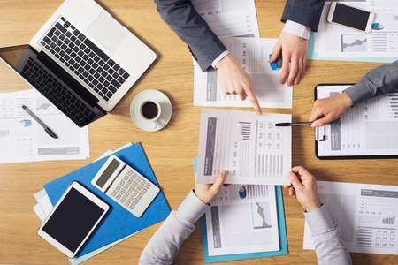 Business people brainstorming at office desk they are analyzing financial reports and pointing out financial data on a sheet top view