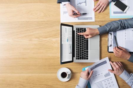 reuniones empresariales: Equipo de negocios manos en el trabajo con los informes financieros y una computadora port�til en blanco copyspace izquierda vista desde arriba Foto de archivo