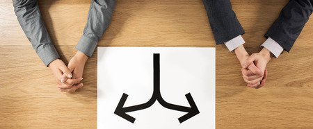 separation: Business man and business woman sitting at desk with hands clasped and a sign with two arrows at center separation and divorce concept hands top view unrecognizable people Stock Photo