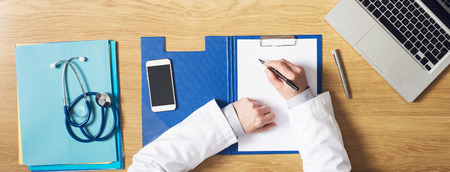 Doctor working at office desk writing medical records on a clipboard hands close up top view
