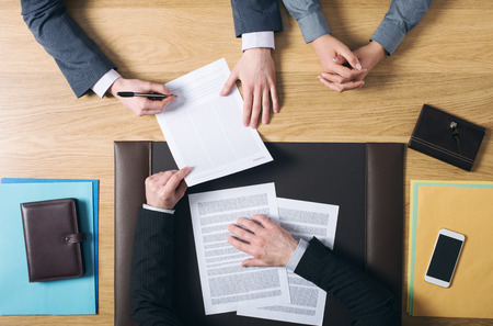Business man and woman sitting at the lawyers's desk and signing important documents hands top view unrecognizable people Stockfoto