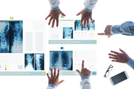 medical records: Professional medical team examining patients medical records and x-ray on touch screen slides and pointing
