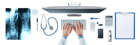 Doctor at desk working at computer with medical equipment on white background, hands close up, top view