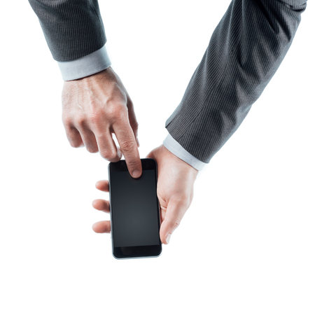 unrecognizable person: Businessman holding a touch screen smart phone and pressing a button on white background, hands close up, unrecognizable person Stock Photo