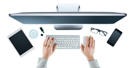 Businessman working at computer at office desk, hands close up top view, white background Stock Photo