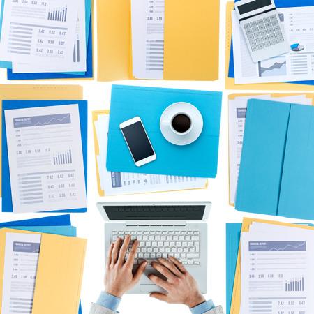 unrecognizable person: Businessman working at desktop on a laptop with financial reports, paperwork and files, top view, unrecognizable person Stock Photo