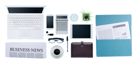 Hi-tech business desktop with computer, smartphone, paperwork and business news, top view on white background Stock Photo