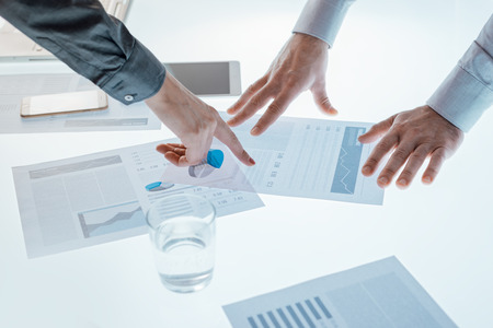 Business people examining financial data on a report and pointing to a chart, hands close up, unrecognizable people photo