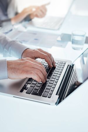 unrecognizable people: Business team working at office desk and typing on a laptop, hands close up, unrecognizable people