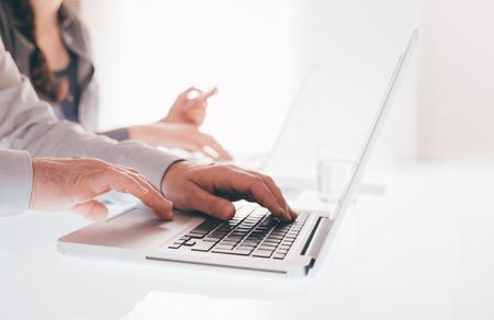 mecanografía: Equipo de negocios trabajando en la oficina escritorio y escribiendo en un ordenador portátil, con las manos cerca, gente irreconocible Foto de archivo