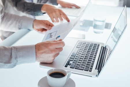 unrecognizable people: Business team working at office desk with laptops and financial reports, hands close up, unrecognizable people Stock Photo