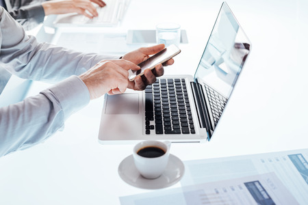Business team working at office desk and businessman using a mobile touch screen smartphone, hands close up photo