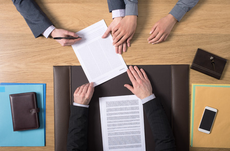 Couple sitting at the notarys desk and signing marriage documents, hands top view, unrecognizable people Stock Photo