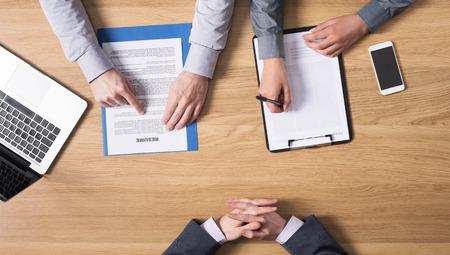 Jeune candidat mâle ayant un entretien d'embauche avec un examinateur femme à ses côtés, les mains en vue de dessus, les gens méconnaissables