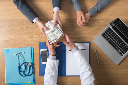 unrecognizable people: Male patient having a medical visit and bribing a greedy doctor with a lot of money, top view unrecognizable people Stock Photo