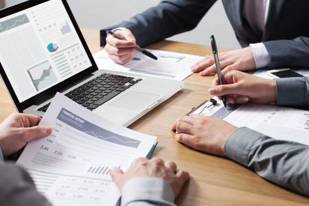 ビジネス プロフェッショナルのオフィスの机で一緒に働いて、手クローズ アップ レポート、チームワークの概念に関する財務データを指摘