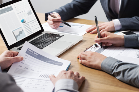 financial graphs: Business professionals working together at office desk, hands close up pointing out financial data on a report, teamwork concept