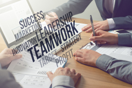 Business professionals working together at office desk, teamwork and marketing text concepts above hands Stock Photo